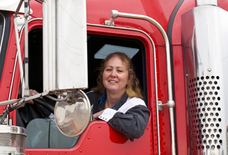 An image of a woman truck driver sitting in her truck, looking out the driver's side window, smiling.