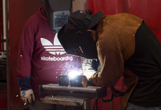 An image of two ACI Fresno welding students working together to weld two metal parts together in class.