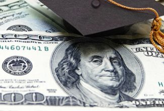 Image of $100 bill showing Benjamin Franklin's face with black graduation cap and gold tassel
