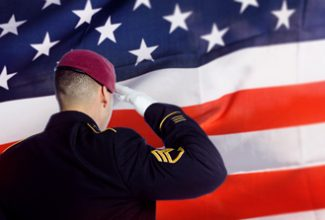 Image of Military service member saluting in front of an American flag background
