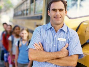 bus driver standing in front of bus with children