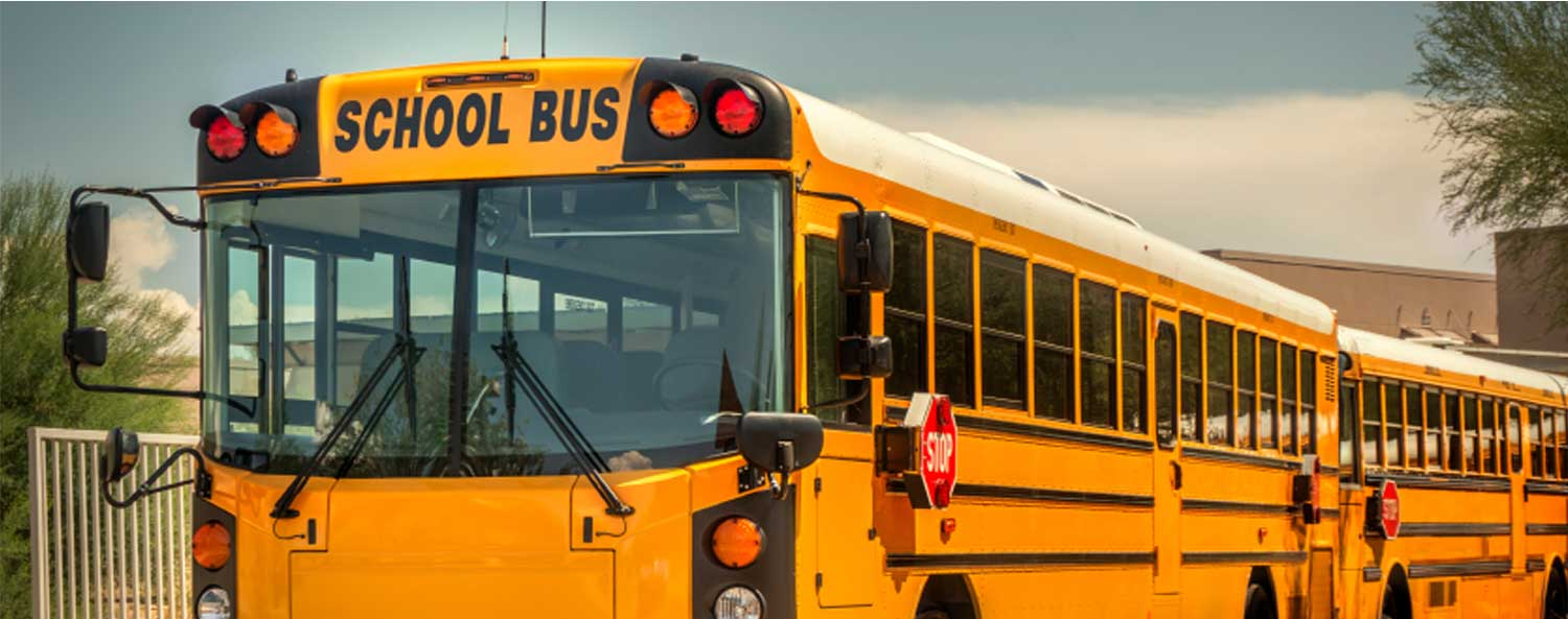 Image of two empty school buses parked one in front of the other.