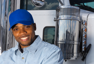 An image of a male truck driver in a blue shirt and hat standing in from of a white truck.