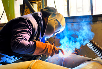 An image of a welder dressed in safety gear welding two pipes together in a lab.