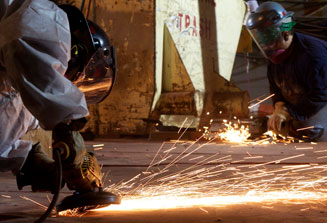 An image of two shipyard welders, kneeling down, dressing in safety gear, welding a section of the ship.
