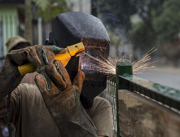 An image of a woman welding a fence at a construction site, wearing proper safety gear.