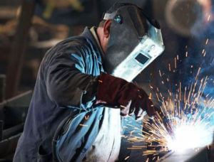 man welding with his helmet on