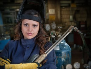 women in welders uniform with blowtorch