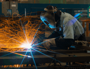 Welder on right welding metal with sparks