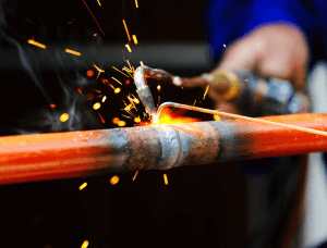 Two cylindrical pieces of metal being welded together with a torch